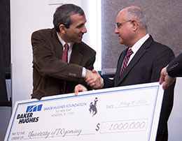 two men shaking hands over an oversized check