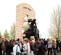 a crowd of people around a statue of a bucking horse and rider breaking through a wall
