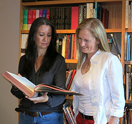 two woman looking at a book in front of bookshelves