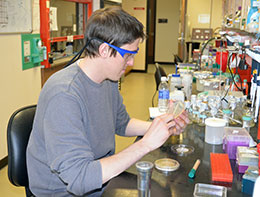 man wearing safety goggles sitting at lab table, using lab equipment