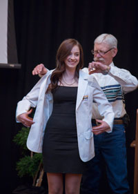 man helping woman put on white coat