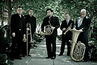 five men holding various brass instruments standing outside under trees on sidewalk