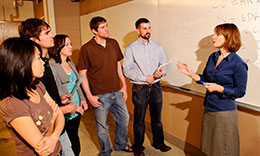 woman talking to group of students by a whiteboard