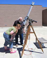 man supervising woman looking through telescope