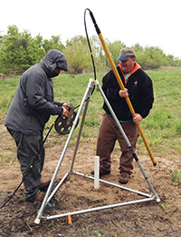 two men setting up a metal triangle shaped apparatus in a field