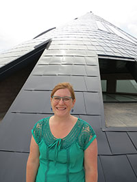 woman standing in front of tee-pee shaped building