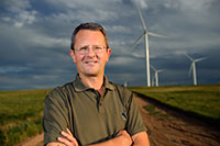 man standing with wind farm in background