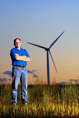 man standing on plains with wind turbine in the background
