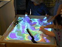 people playing in sandbox with projected colors for height variations in sand