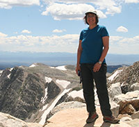 woman standing on a rock with rugged rocky mountain tops in the background