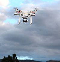 drone with camera flying with clouds behind it