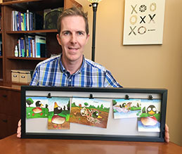 A man sitting at a table and holding up a framed set of illustrations of a duck