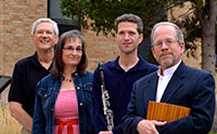 three men and one woman standing with a clarinet and a wooden flute