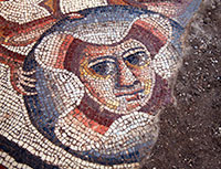 ancient mosaic of face still partly covered with dirt