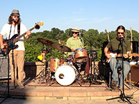 three men with guitars and drum set on an outdoor stage