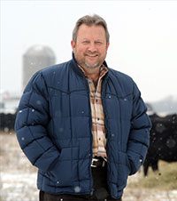 man standing outside in snowfall with cattle and silos in the background