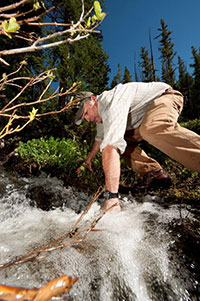 man reaching into rushing stream