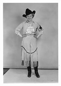 black and white vintage photo of a woman in a cowboy hat and fringed skirt