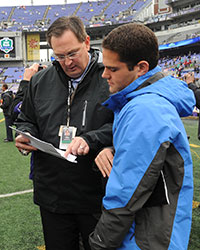 two men looking at paperwork on the sidelines of a football game