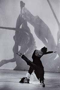 two people doing modern dance with images projected behind them