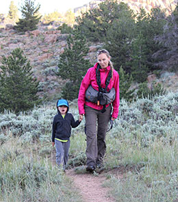 woman and small child walking on mountain trail