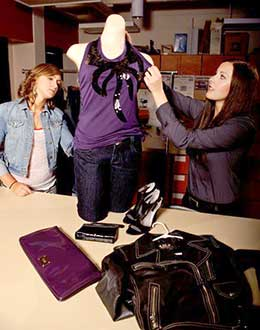 two young women adjust clothing on mannequin on table
