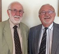 two older men in ties and jackets standing beside each other