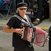man walking in crowd and playing an accordion