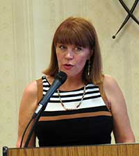 woman talking into a microphone at a podium