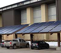 solar panels outside a building with vehicles parked under them