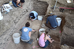 overhead view of people kneeling in the dirt and excavating an archaelogical site