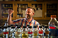 man in lab with bottles of colorful liquid in front of him