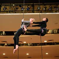 young man and woman on lhanging from harnesses for vertical dance