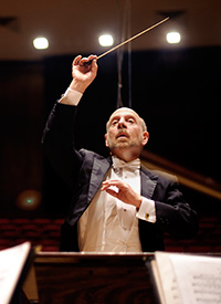 man in white tie and tails with baton raised conducting an orchestra