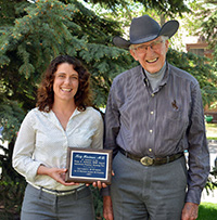 woman holding plaque and standing beside older man