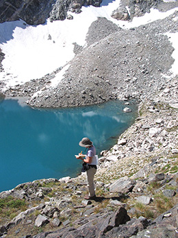 overhead view of person standing by mountain lake