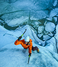 overhead view of man climbing up an ice wall with picks