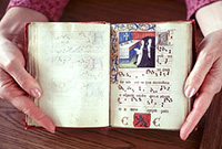 person's hands holding open a medieval text