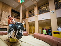 man riding a mechanical bull while other people watch