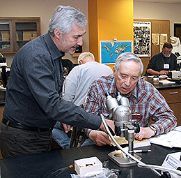 two men, one at a microscope, the other leaning over and talking to him