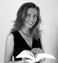 woman holding an open book and smiling at camera
