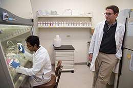 man leaning against counter watching man in chair work in lab