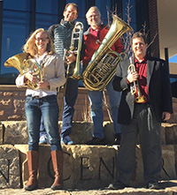 four people holding brass instruments posing outside