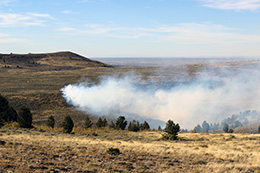 smoke coming up from rolling prairie landscape
