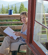 woman sitting on deck in mountains and holding papers