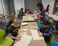 children at two long tables making things with paper