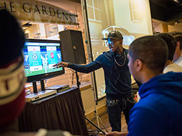 man standing and pointing to images on video screen while others look on