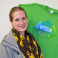 woman posing beside a t-shirt that says WYSTEM