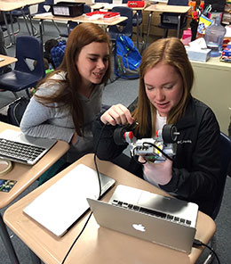 two girls using computers and working with small wheeled robot