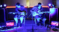 two men sitting on stools and playing guitars with amplifiers around them